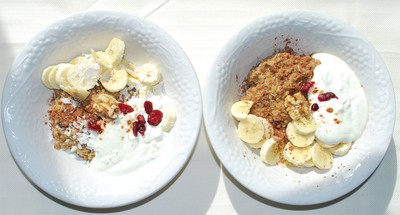 served with banana, yogurt, cacao powder, a walnut and cranberries for decoration.